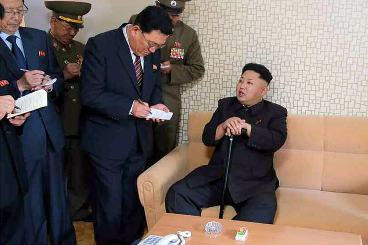 Kim Jong-un istuu sohvalla kävelykepin kanssa, seurue kirjoittaa lehtiöihinsä