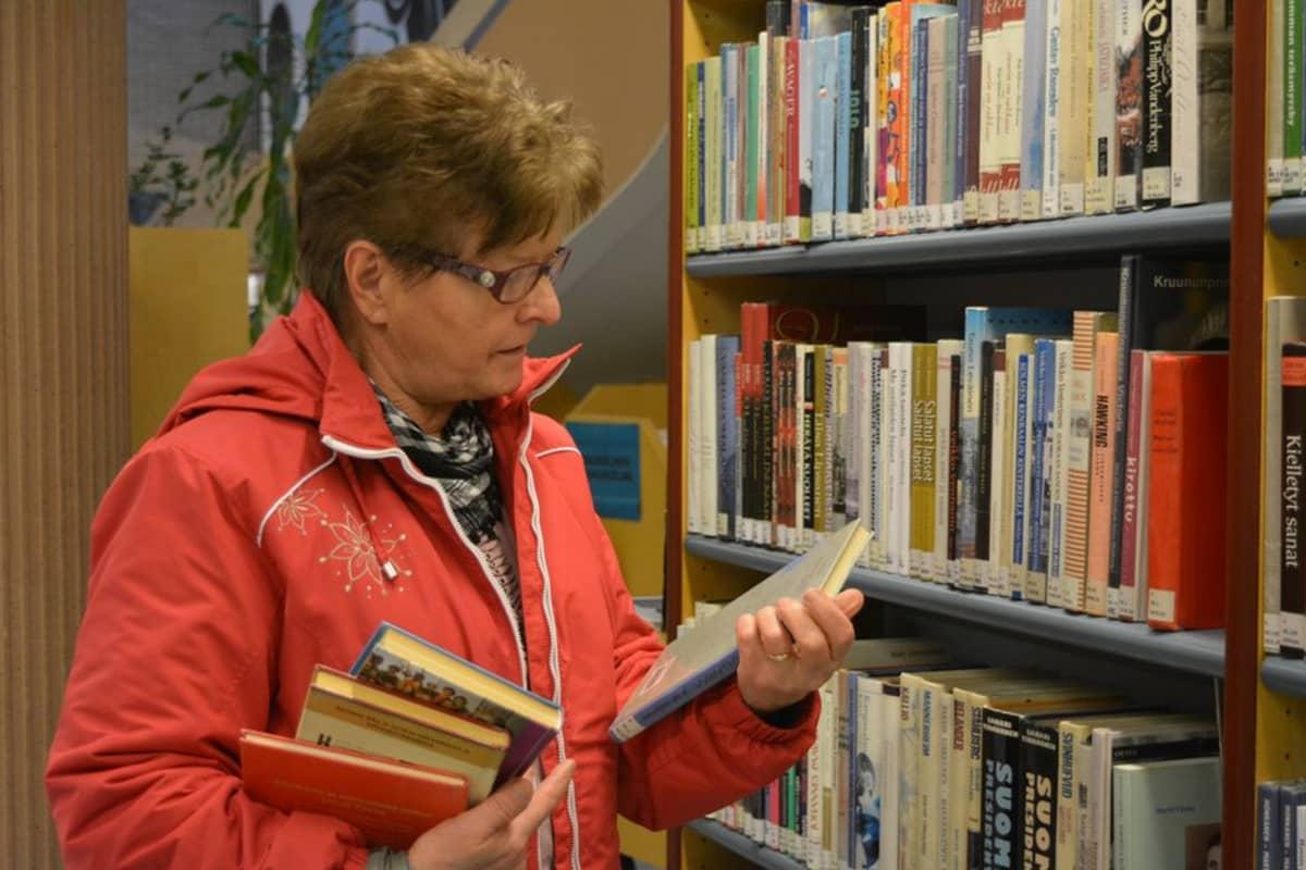Nainen lukee kirjan takakantta kirjastossa.