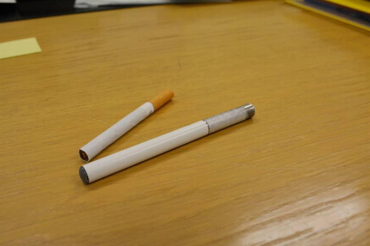 Sähkötupakka ja tupakka vierekkäin.