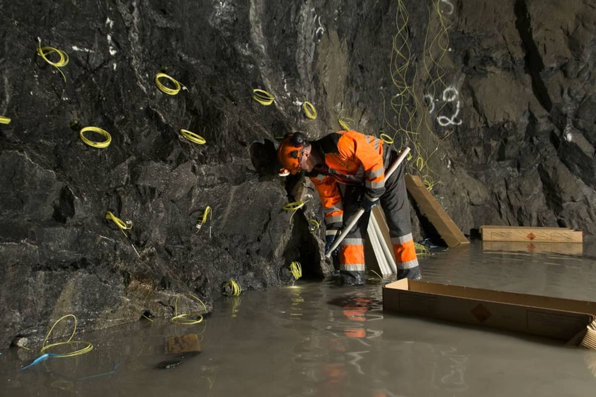 Panostaja laittaa räjähteitä kallioon tunnelityömaalla.