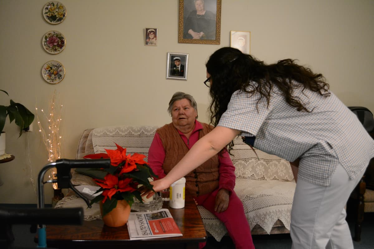 Nainen istuu sohvalla, hoitaja kurkottaa hänen eteensä olevan pöydän päälle.