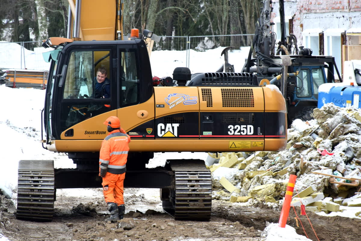 Kaivinkone ja kaksi miestä rakennustyömaalla