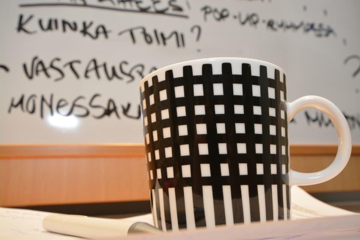 Kahvikuppi ja kokouksen muistiinpanoja