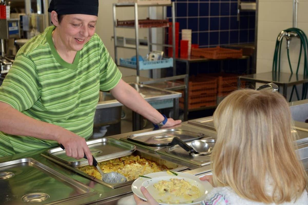 Lumijoen koulun kokki Anna-Maija Lukkarila tarjoilee oppilaalle broilerikiusausta.