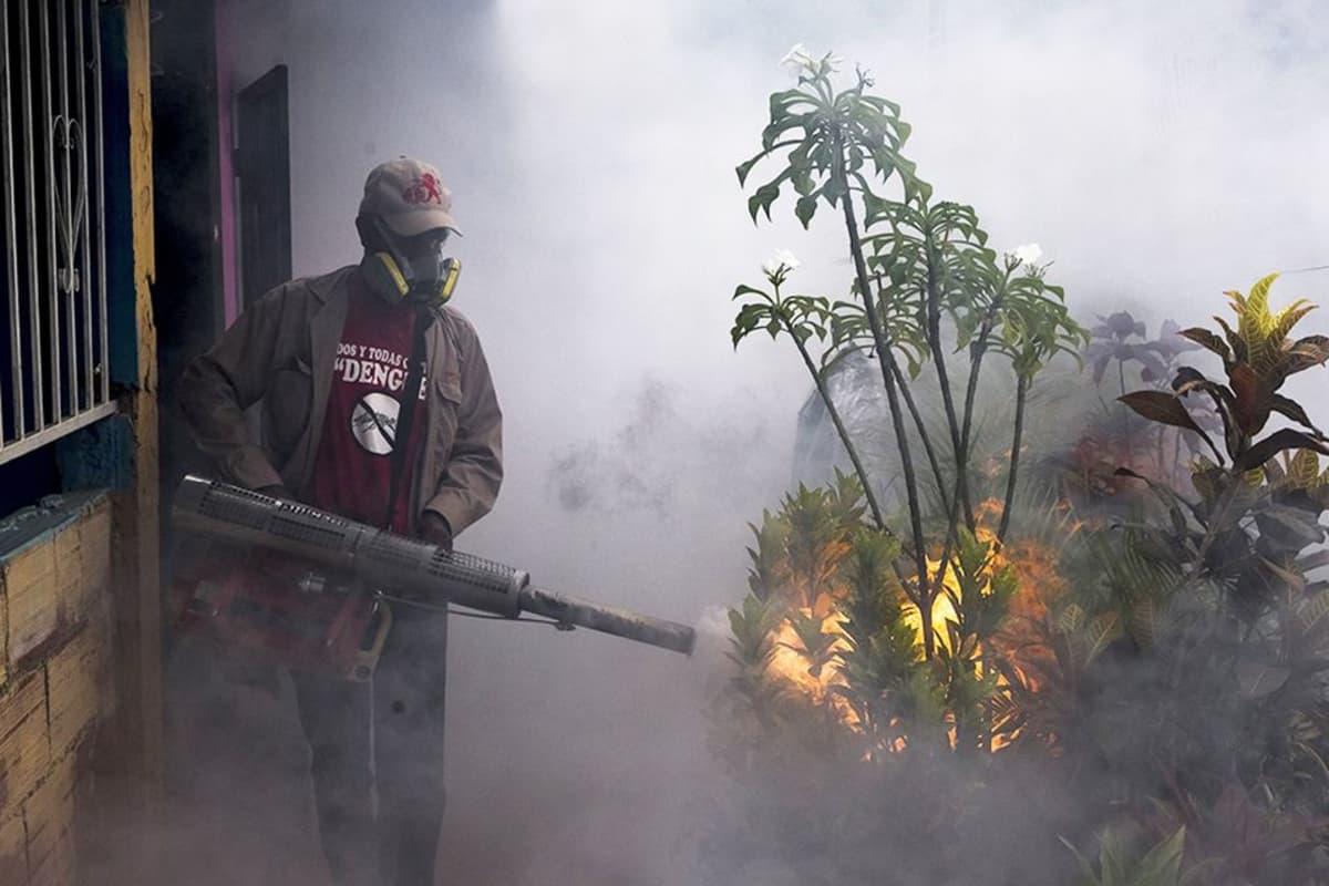 Miehellä on kädessään häkäpöntön ja konekiväärin hybridiltä näyttävä laite, joka syöksee putkestaan savua ja tulta. Miehellä on hengityssuojain ja lippalakki päässään.