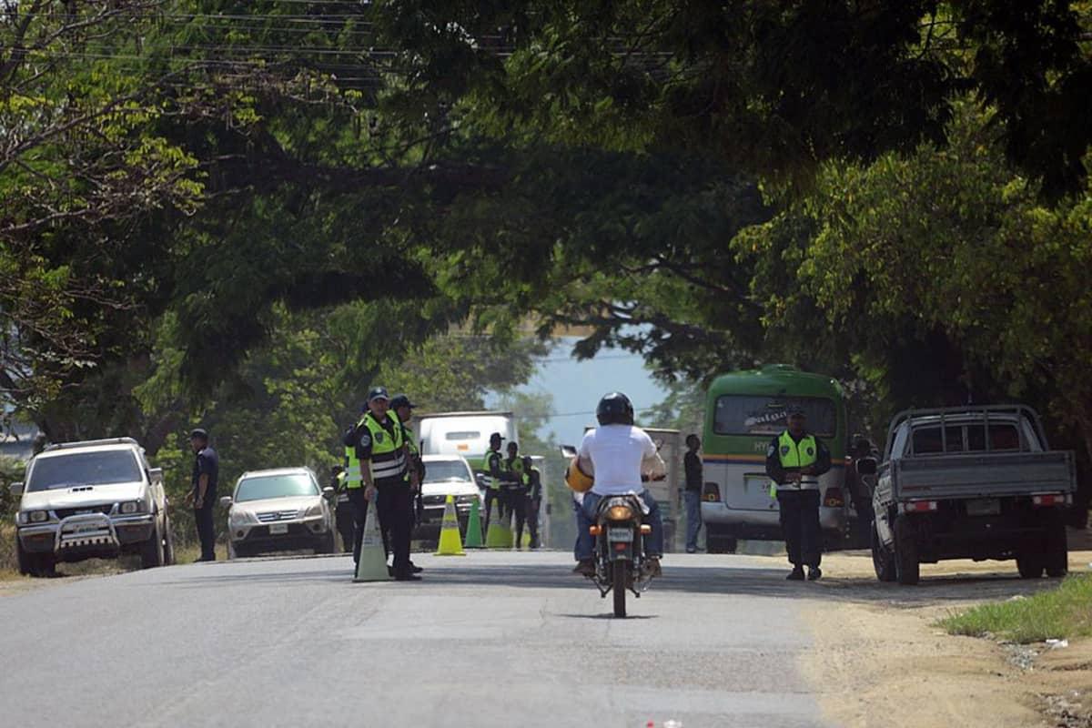 Useita poliiseja seisoo tiellä. Tien varressa on linja-auto ja useita muita autoja. Tiellä ajaa mopo.