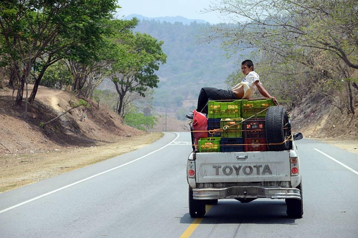 Hedelmäkoreja kuljettava avolava-auto ajaa vuoristotietä. Kuorman päällä istuu poika.