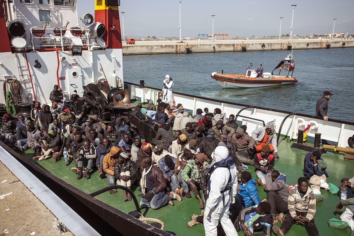 Italian rannikkovartiosoto tuo pelastettuja maahanmuuttajia satamaan.