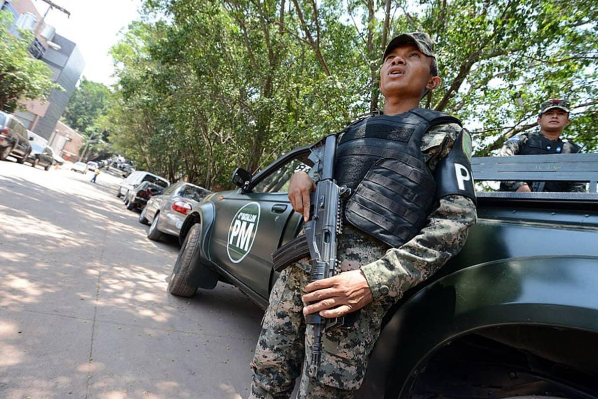Sotilaspoliisit valvovat, etteivät kilpailevat jengit ota yhteen Tegucigalpan ruumishuoneella.