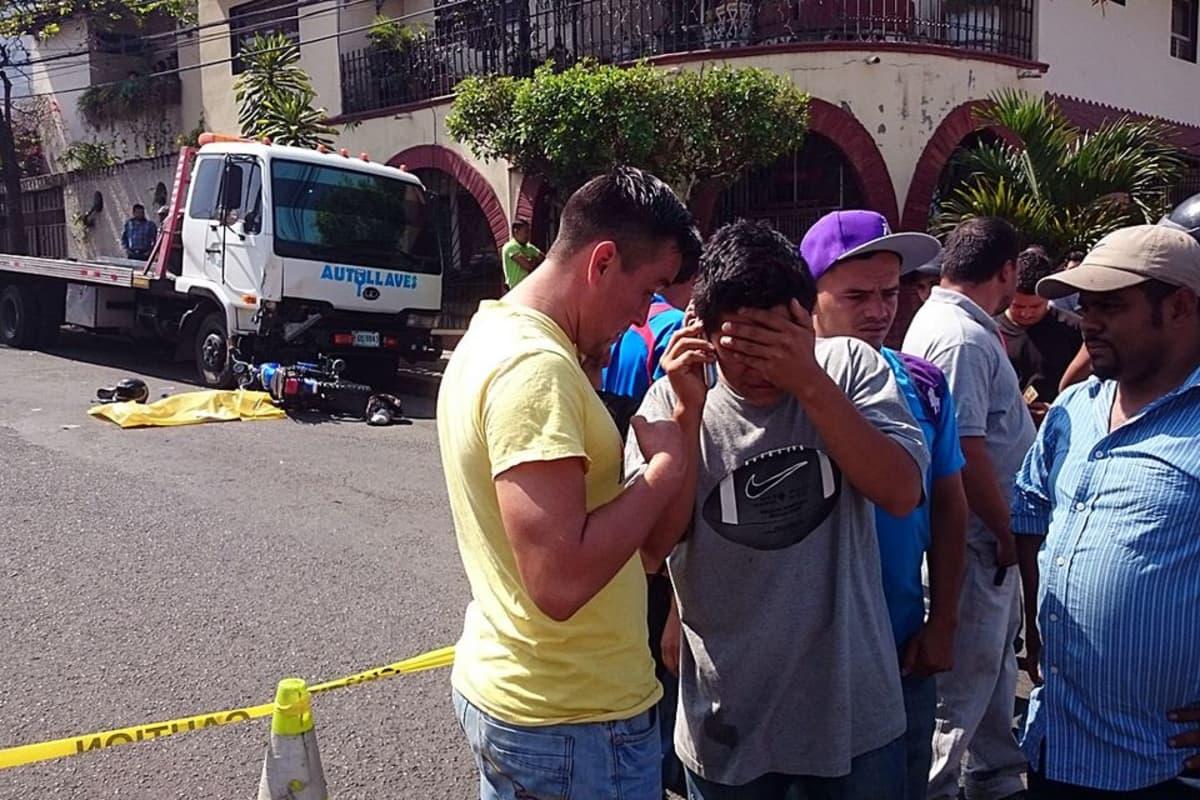 Surevia miehiä seisoo kadulla onnettomuuspaikan vieressä.