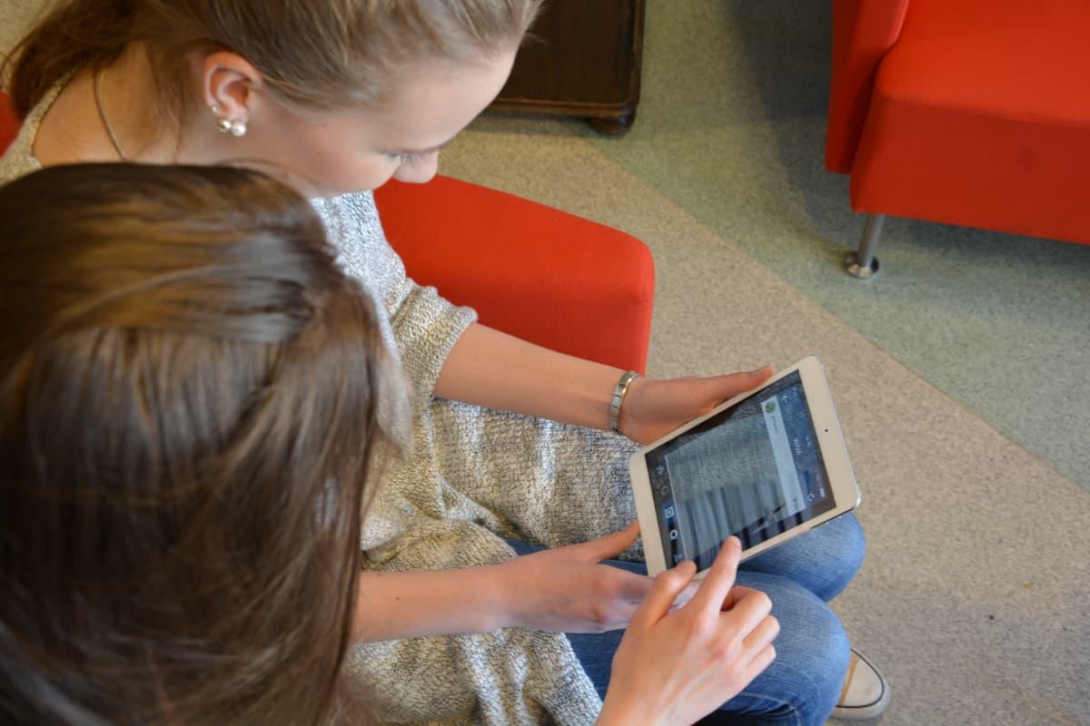 Aleksia Kulluvaara ja Elli Lehtimäki selaavat tabletilla.