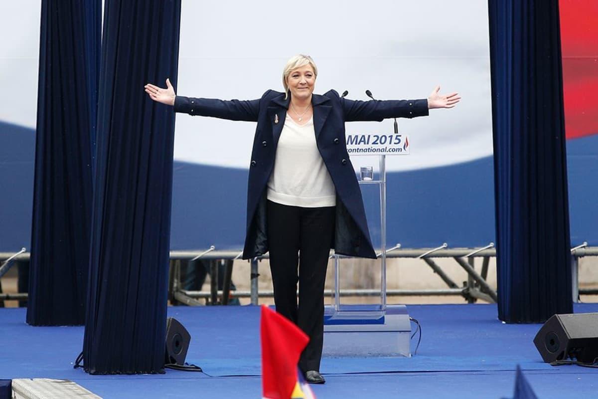 Ranskan kansallisrintaman johtaja Marine Le Pen puhujalavalla kädet levitettyinä