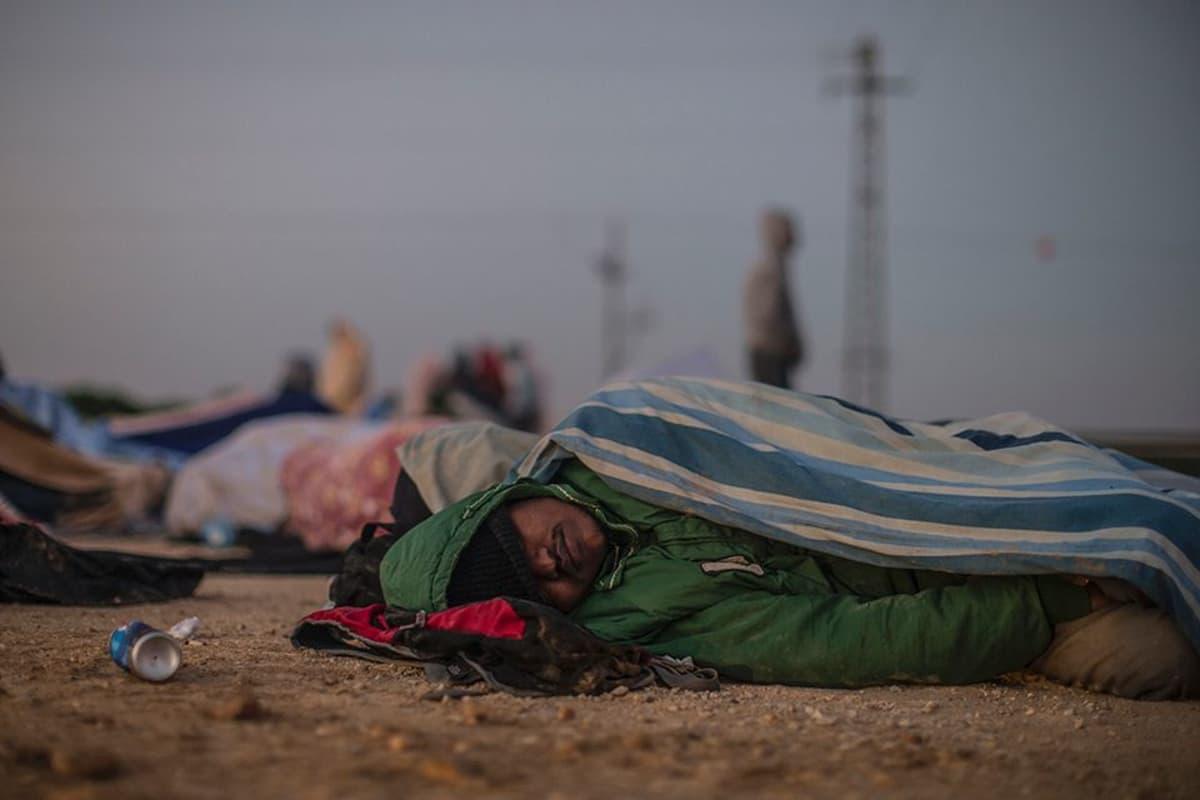 Afrikkalainen turvapaikanhakija nukkuu Holotin vankilan ulkopuolella Negevin autiomaassa.