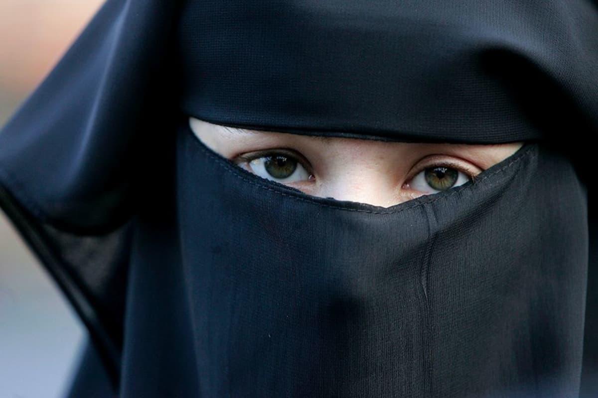 Naisen yllä burka ja nigaabs.