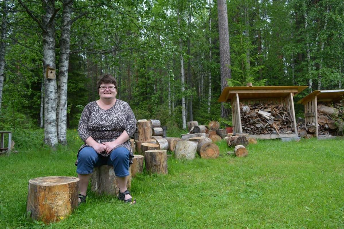 Miia Korhonen istuu laitoskotinsa takapihalla puupölkyllä.