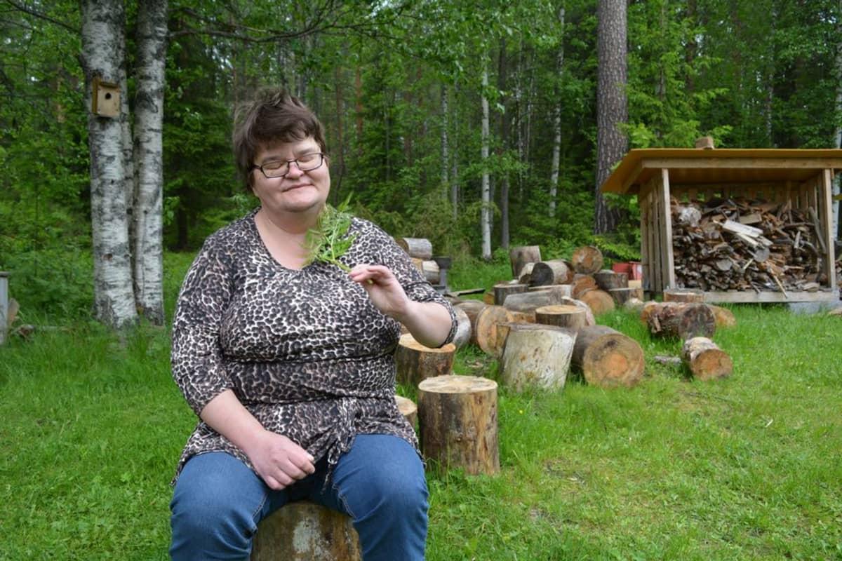 Miia Korhonen istuu laitoskotinsa takapihalla puupölkyllä ja huitoo hyttysiä lehdellä.