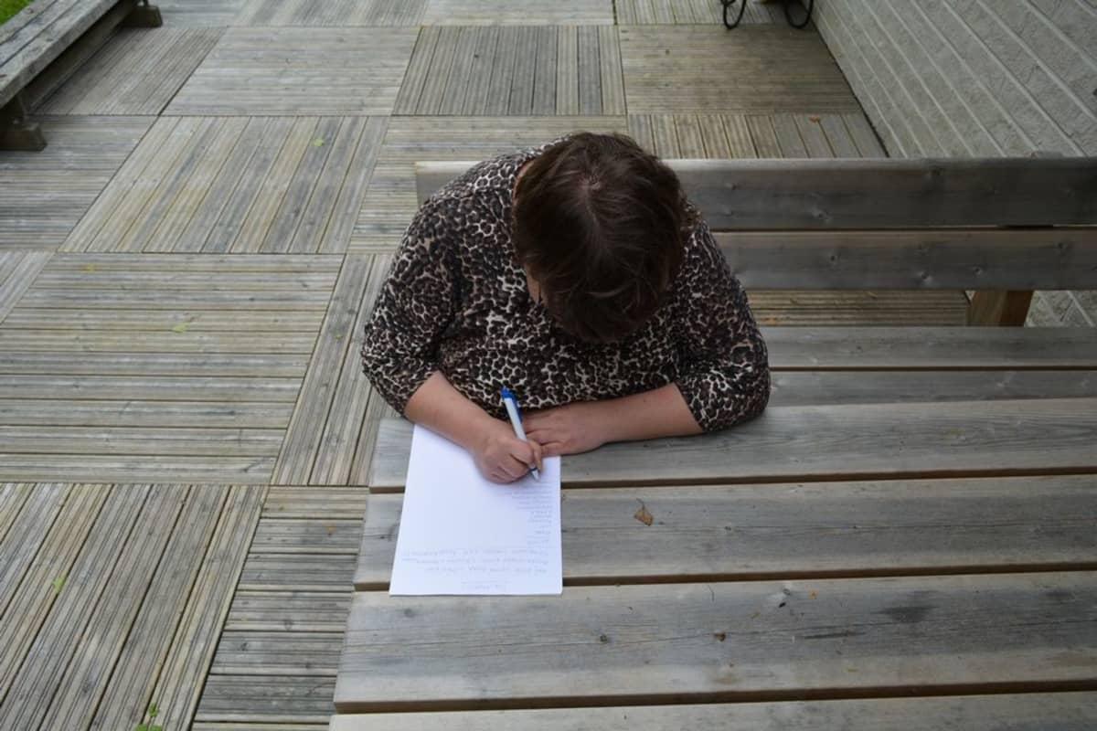 Miia Korhonen listaa paperille haaveitaan tulevaisuuden omaan kotiin hankittavista asioista.
