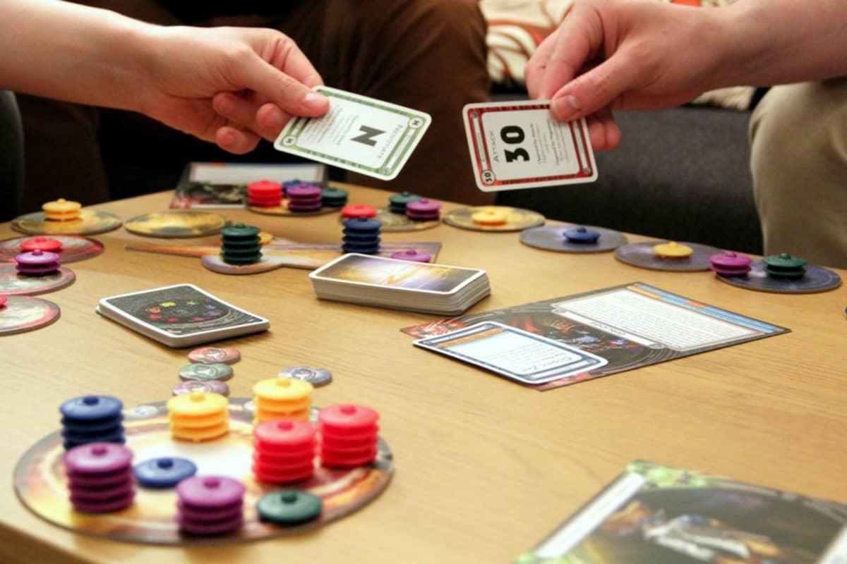 Ihmisiä pelaamassa lautapeliä ja näyttämässä korttejaan