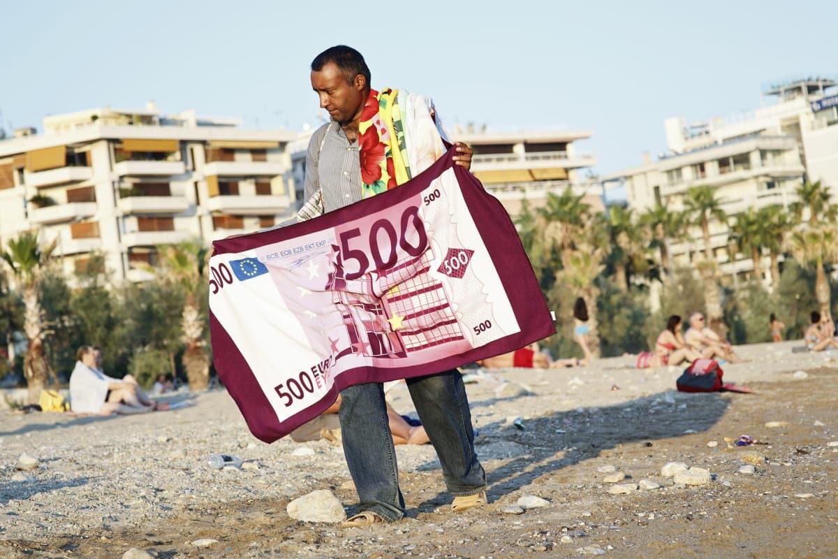 Mies kävelee Ateenan edustalla rannalla kädessään pyyhe, jossa on 500 euron setelin kuva.