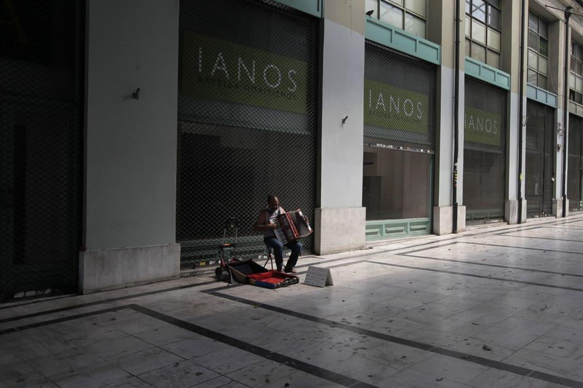 Yksinäinen katumuusikko autiolla ateenalaisella kadulla.