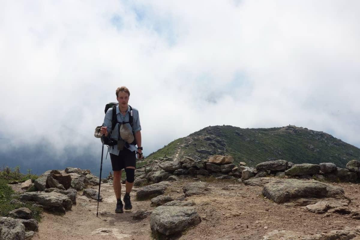 Mies vaellussauva kädessään vuoren harjanteella.