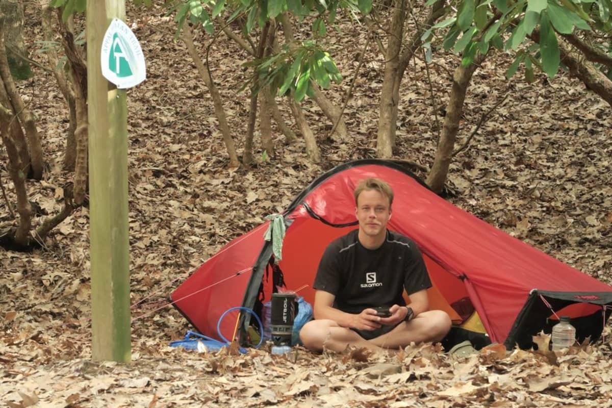 Nuori mies istuskelee teltan edessä puita ympärillään.