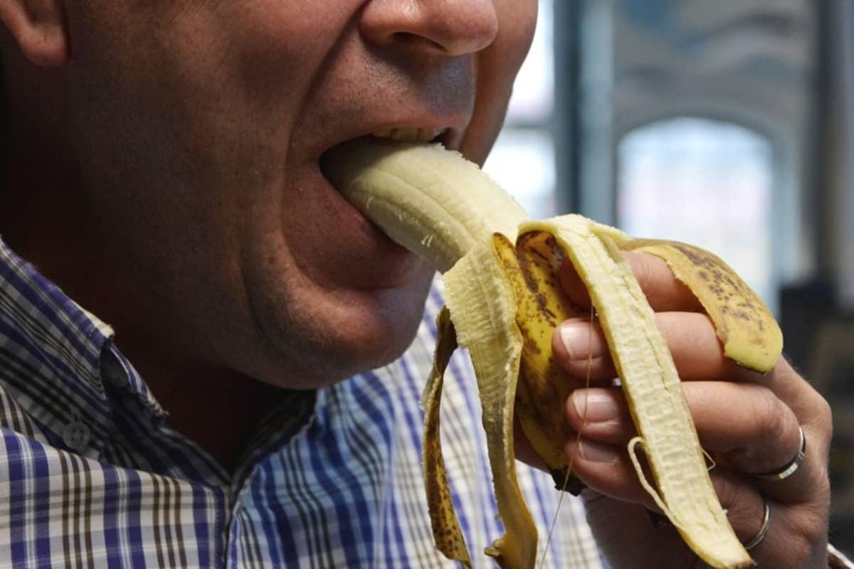 Mies syö banaania