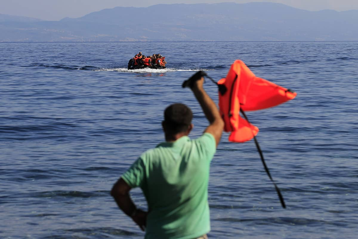 Kreikkalaismies viittoo turvapaikanhakijoille