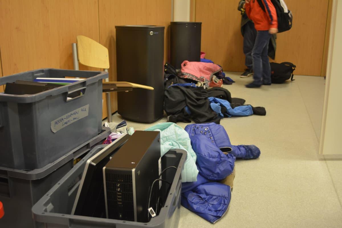 Vaatteita ja laatikoita messukeskuksen käytävällä.