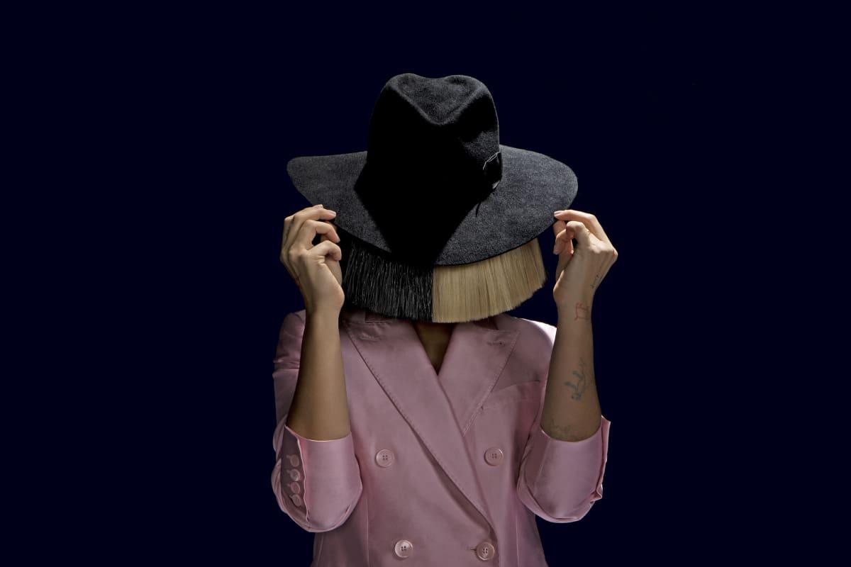Nainen hattu päässä kasvot kokonaan hiusten peitossa