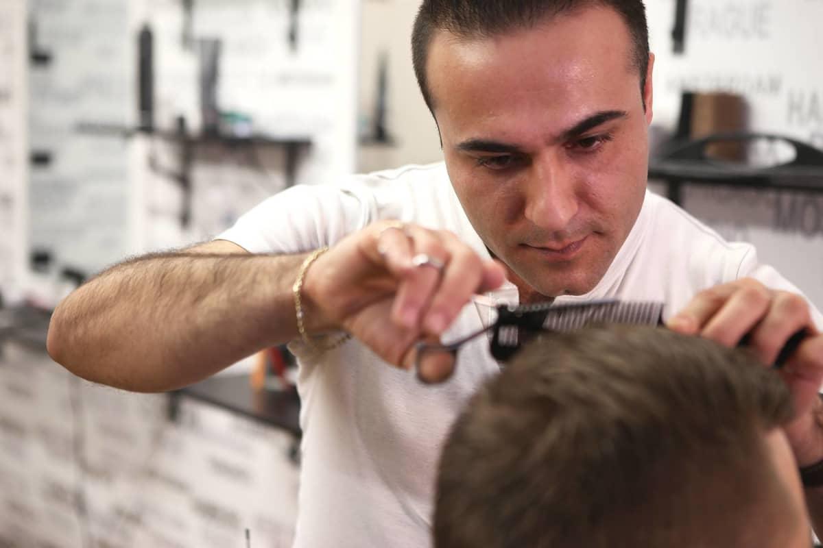 Kurdilainen Solyiman Ibrahimpoor leikkaa asiakkaan hiuksia.