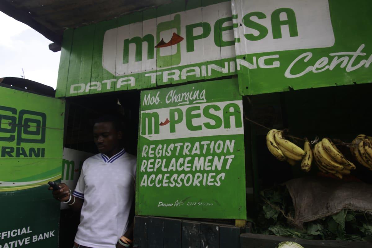 Mies näprää puhelintaan M-Pesa-kioskin edessä Nairobissa.