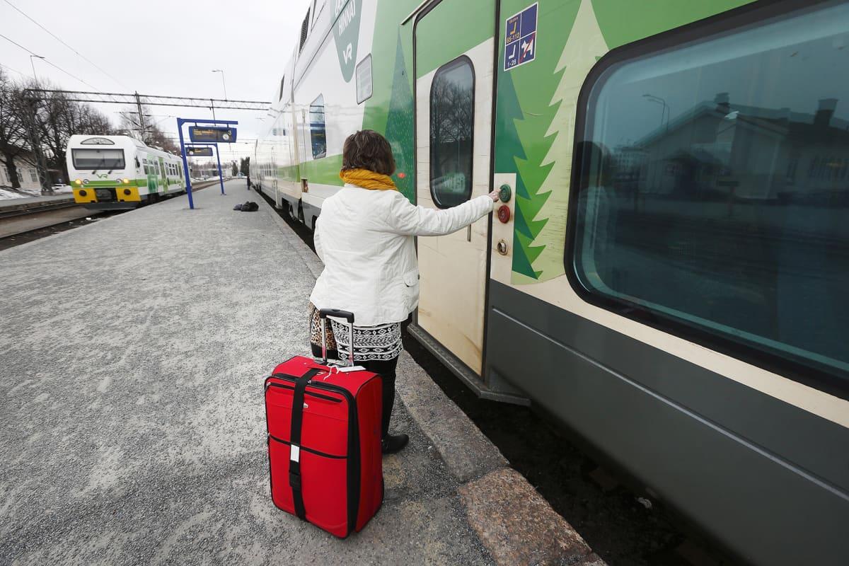 Nainen menossa matkalaukkuineen junaan.
