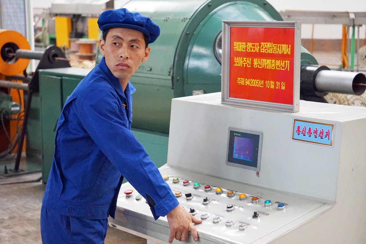 Mies työskentelee kaapelitehtaalla