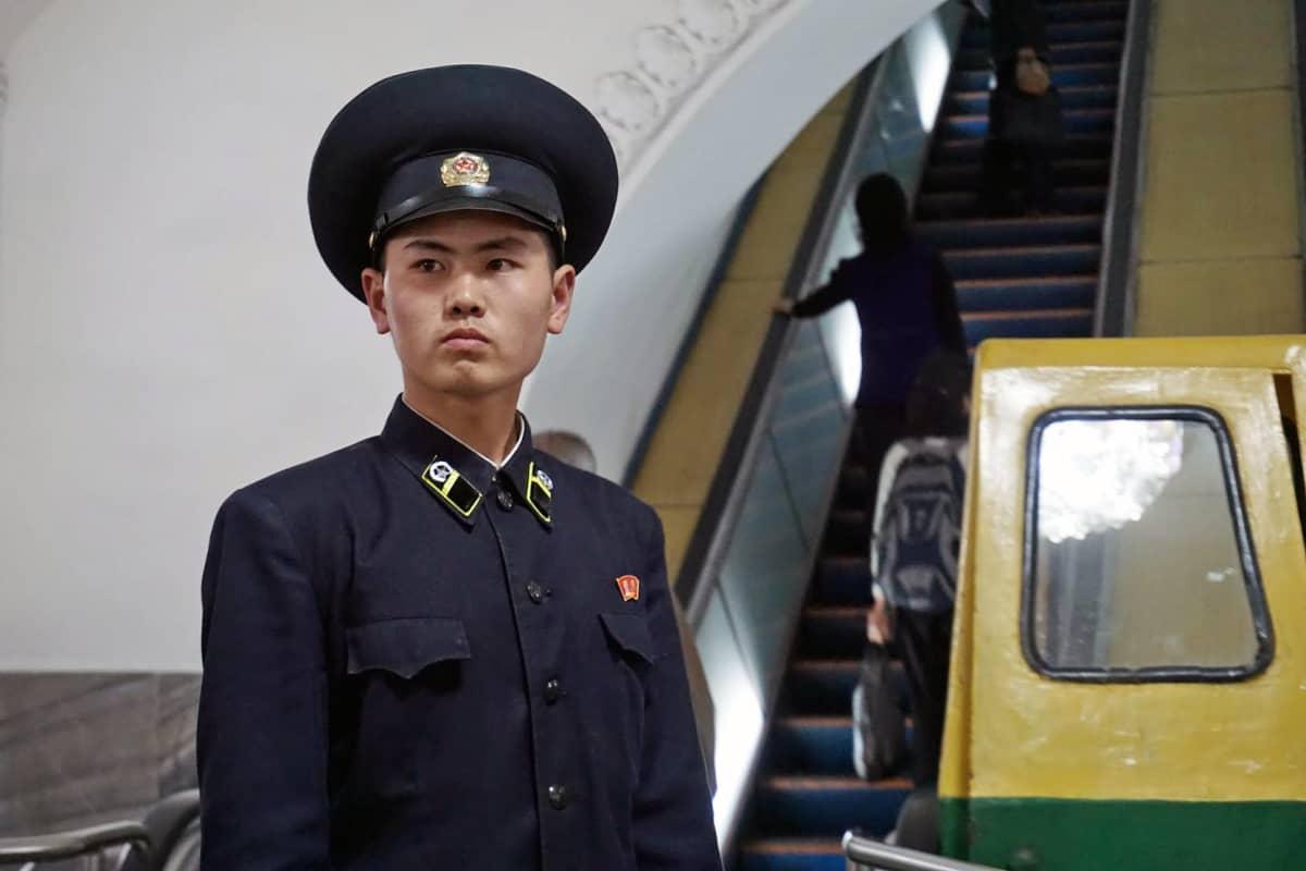 Pjongjangin metron vartija tarkasti, että ihmiset nousivat oikeita liukuportaita ylös.
