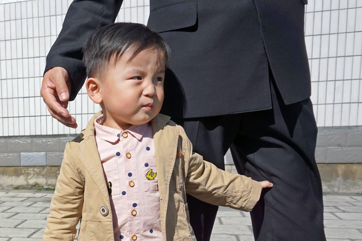 Lapsi haki turvaa isänsä housunlahkeista Yonggwangin metroaseman sisäänkäynnin luona.