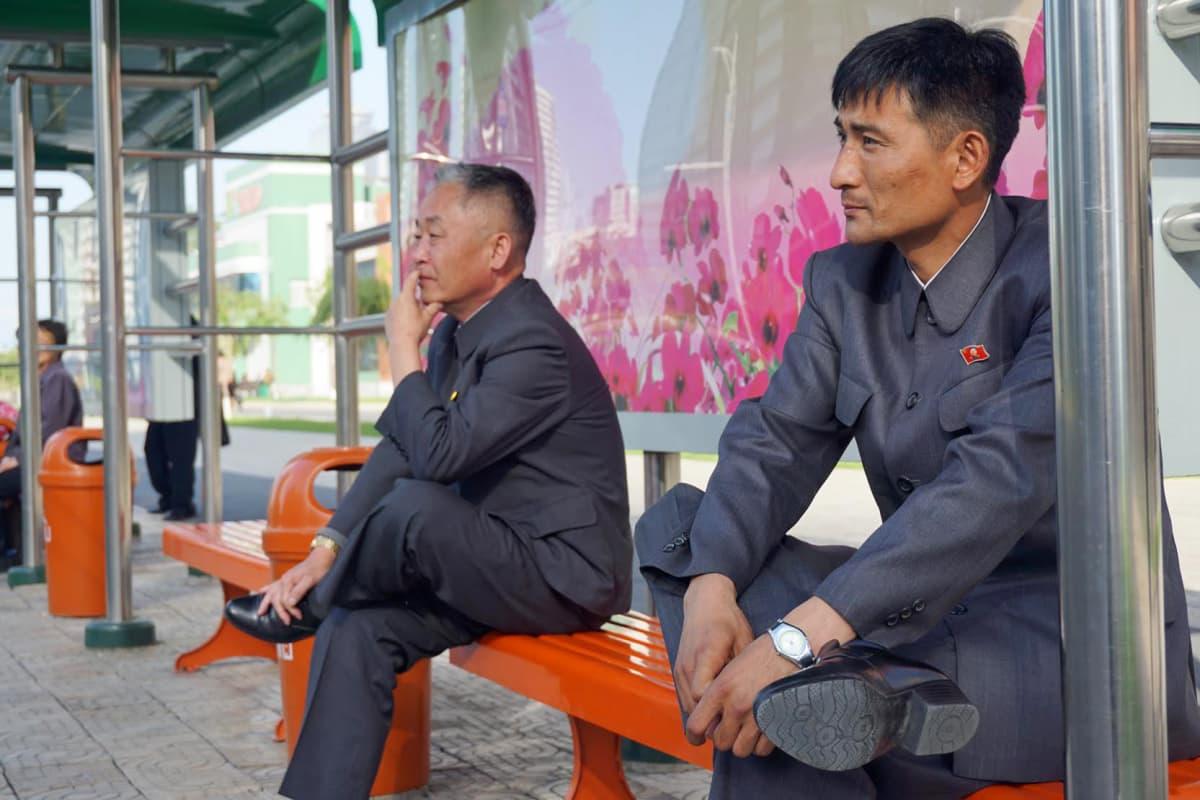 """Miehet istuvat upouudella bussipysäkillä """"Tulevaisuuden tiedemiesten kadun"""" pilvenpiirtäjäalueella."""