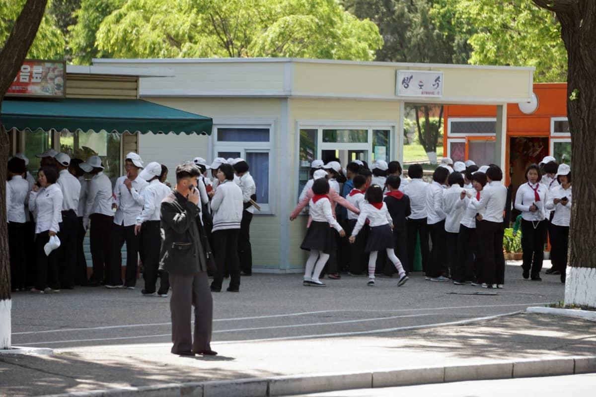 Univormuun pukeutuneet nuoret jonottivat kioskin edustalla Pjongjangissa.