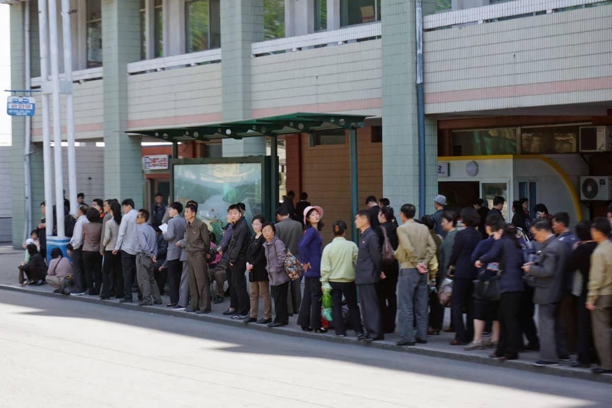 Pohjoiskorealaiset jonottivat bussipysäkillä  Pjongjangissa.