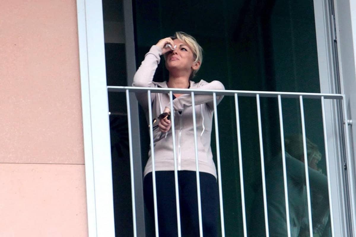 Nuori vaalea hiuksinen nainen katsoo ikkunasta ulos pyyhkien nenäliinalla silmäänsä.