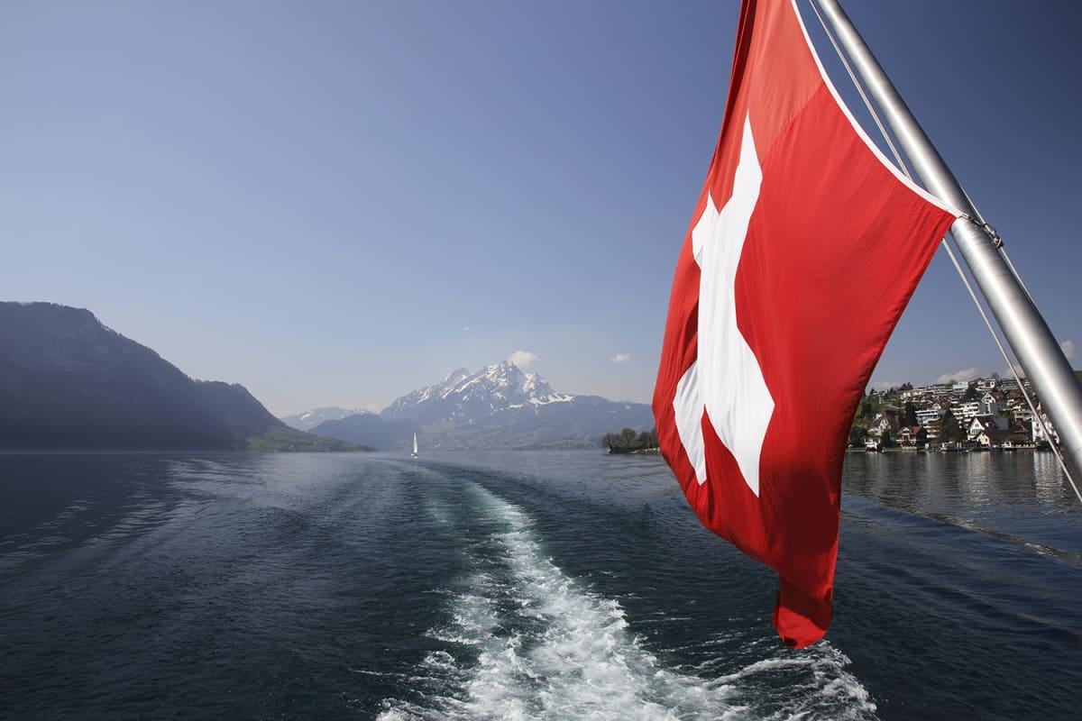 Sveitsin lippu veneen perässä.