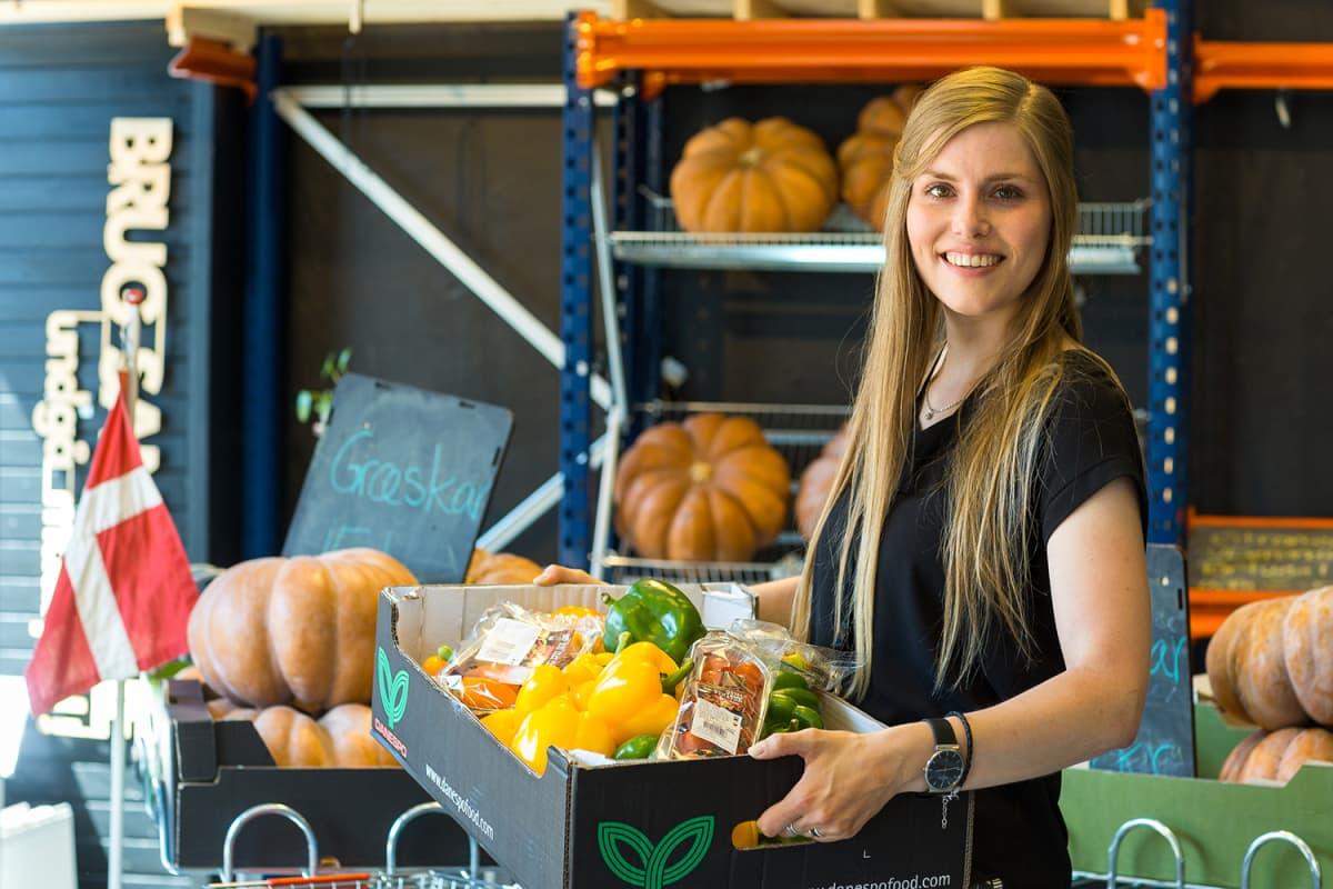 Nainen kantaa vihanneksia pahvilaatikossa.