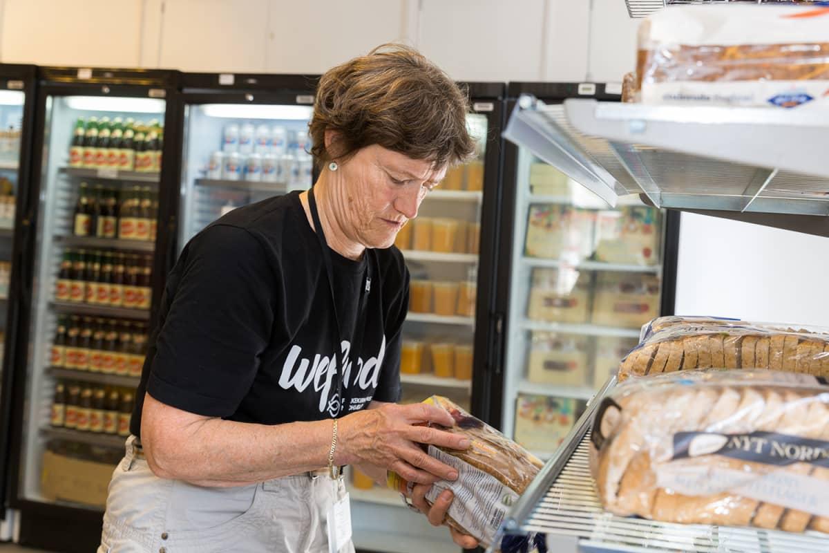 Nainen tutkii leipäpakettia kaupassa.