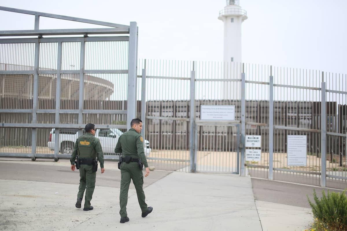 Vartijat kävelevät kohti Yhdysvaltojen ja Meksikon välistä rajavyöhykettä eristävää aitaa.