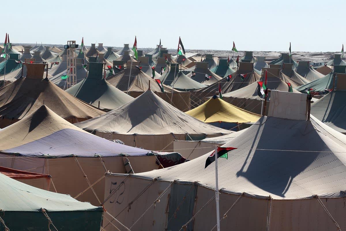 Telttoja keskellä autiomaata, telttojen katoilla lippuja.