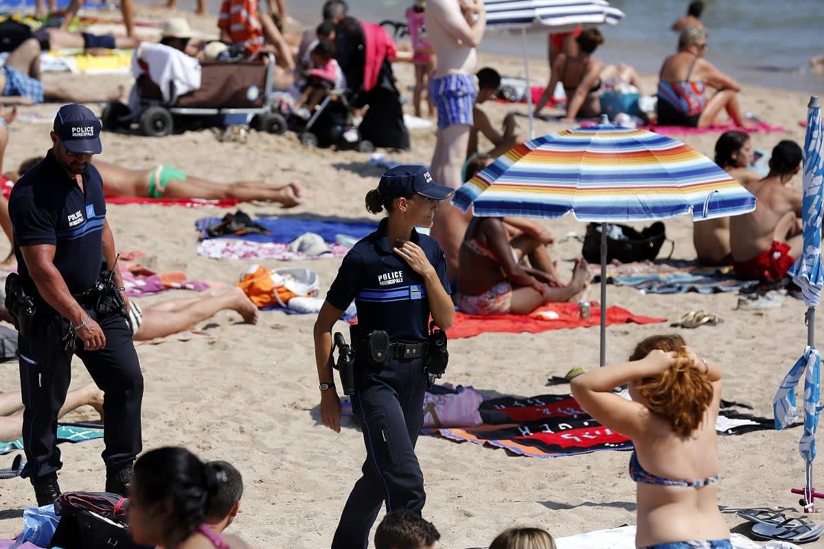 Kaksi poliisia kävelee rantahiekalla ihmisten lomassa.