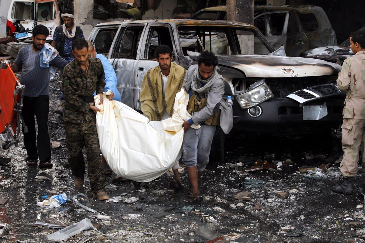 Yemeniläisiä miehiä kantamassa kuollutta henkilöä ulos raunioista.