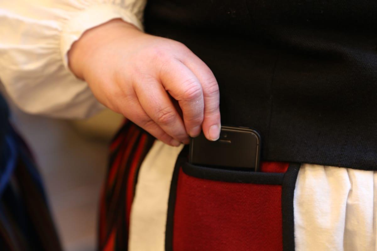 Kansallispuvun tasku soveltuu nykypäivänä vaikka kännykän säilytykseen.