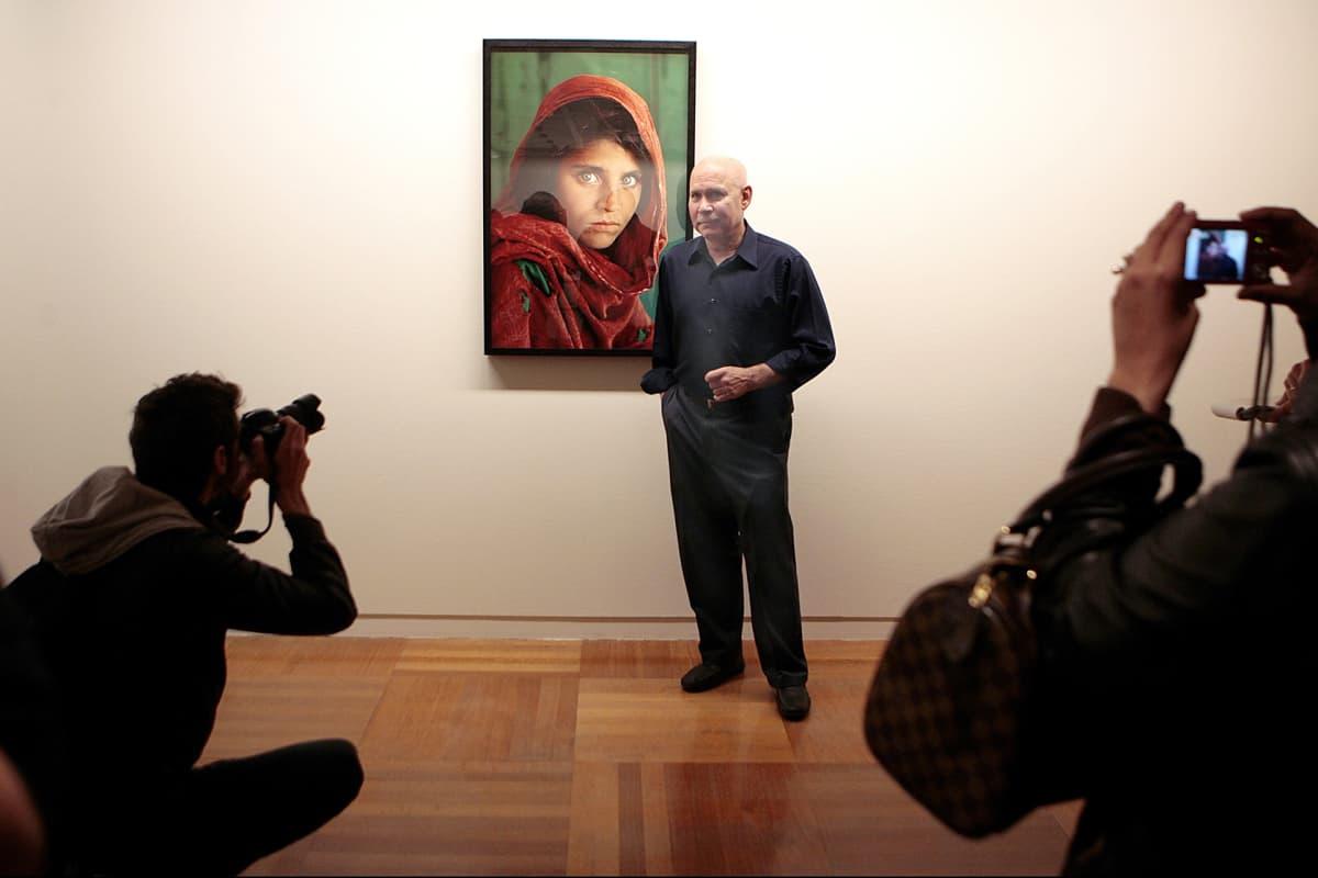 Valokuvaaja Steve McCurry kuvattuna maailmankuulun teoksensa 'Afghan Girl' (1985) vierellä restrospektiivinsä avajaisissa Santa Cruzissa, Teneriffalla, 13. maaliskuuta 2012.