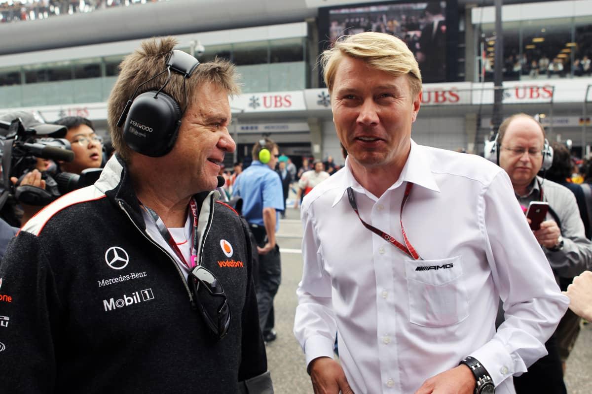 McLarenin lääkäri Aki Hintsa ja Mika Häkkinen hymyilevät F1-varikolla vuonna 2012.